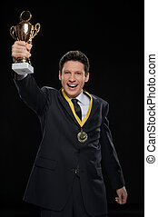 His first business award. Happy businessman showing off a trophy while standing against black background