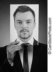 His today mask. Black and white image of man in formalwear holding a photograph of serious man in front of his face