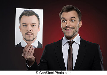 His today mask. Cheerful young man in formalwear holding a photograph of himself while isolated on red