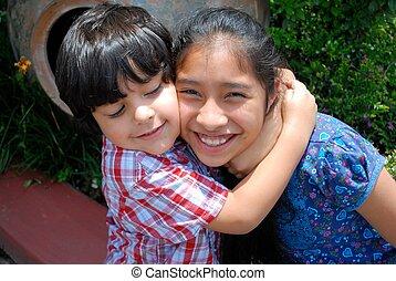 Hispanic boy hugging his sister