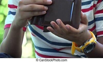 Hispanic Boy Openning Wallet or Billfold
