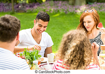 Hispanic boy smiling and sitting next to a girl who is eating a watermelon during a garden party