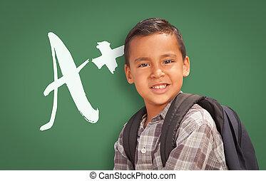 Hispanic Boy Up in Front of A+ Written on Chalk Board