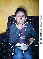 Hispanic boy  with popcorn watching television