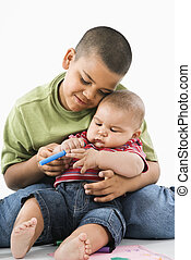 Hispanic brothers cuddling. - Young latino boy holding baby...