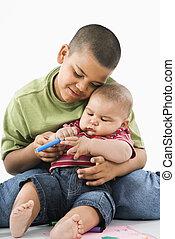 Hispanic brothers cuddling. - Young latino boy holding baby...