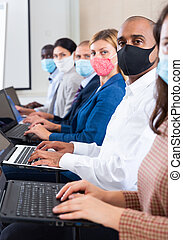Hispanic businessman in mask with laptop during business training