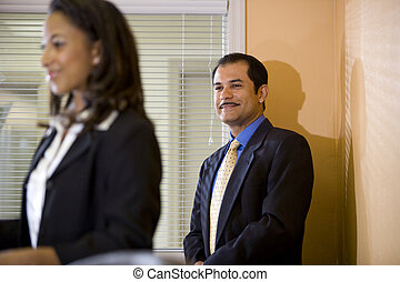 Hispanic businessman looking at businesswoman in boardroom