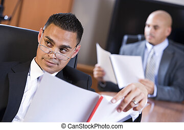 Hispanic businessmen in boardroom reviewing report