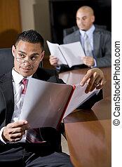 Hispanic businessmen in boardroom reviewing report, watching...