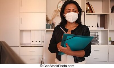 Hispanic Latin american female business assistant wearing medical face mask standing in office with clipboard, noting tasks. Concept of social distance in coronavirus pandemic businesswoman in protective face mask holding folder with papers, writing tasks and instructions. New life reality during ...