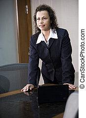 Hispanic businesswoman standing in boardroom