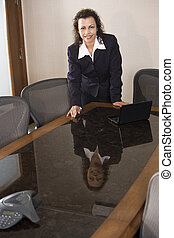 Hispanic businesswoman standing in boardroom