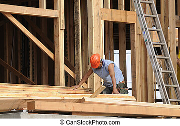 Hispanic Carpenter sorting wood just put in place by a fork lift