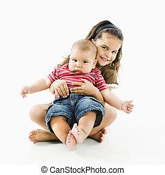 Hispanic child holding baby. - Cute little hispanic girl...