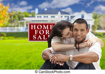Hispanic Couple, New Home and For Sale Real Estate Sign