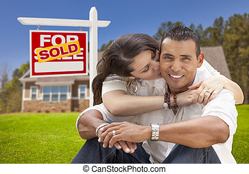 Hispanic Couple, New Home and Sold Real Estate Sign - Young...