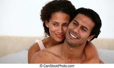 Hispanic couple sitting on the bed