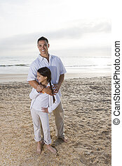 Hispanic dad and girl standing together on beach