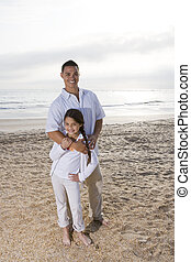 Hispanic dad and girl standing together on beach