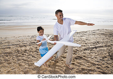 Hispanic dad, girl playing with toy plane on beach -...