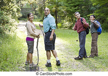 Hispanic family hiking in woods on trail - Hispanic family...
