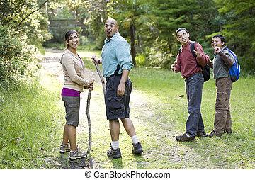 Hispanic family hiking in woods on trail - Hispanic family...