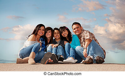 Hispanic Family - Hispanic family seated against a cloudy...