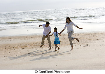 Hispanic family holding hands skipping on beach