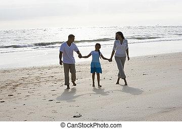 Hispanic family holding hands walking on beach