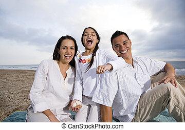 Hispanic family sitting on blanket at beach - Latin American...
