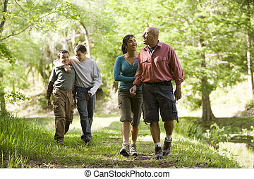 Hispanic family walking along trail in park - Happy Hispanic...