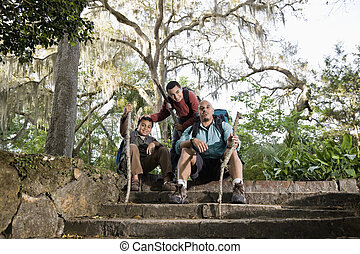 Hispanic Family With Backpacks Hiking In Park