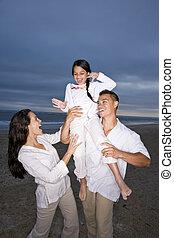 Hispanic family with daughter having fun on beach