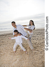 Hispanic family with girl having fun on beach
