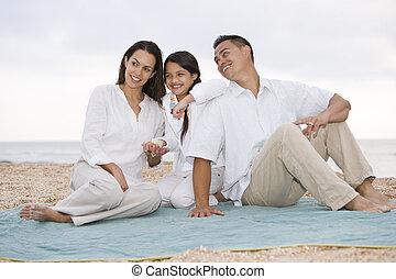 Hispanic family with little girl on beach blanket