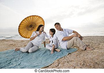 Hispanic family with little girl on beach blanket - Hispanic...
