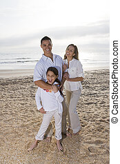 Hispanic family with little girl standing on beach -...