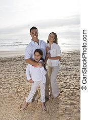 Hispanic family with little girl standing on beach
