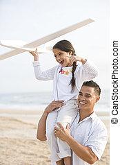 Hispanic father and daughter having fun on beach