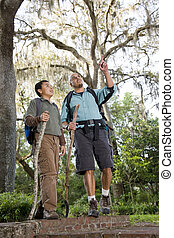 Hispanic father and son hiking in park