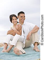 Hispanic father with little girl on beach blanket