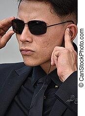 Hispanic Fbi Agent Listening Wearing Sunglasses