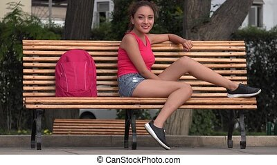 Hispanic Female College Student Sitting On Park Bench
