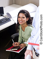 Hispanic female office worker sitting at cubicle desk