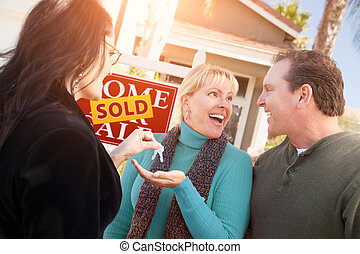 Hispanic Female Real Estate Agent Handing Over New House Keys to Happy Couple In Front of Sold For Sale Real Estate Sign