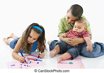 Hispanic girl coloring with brothers.