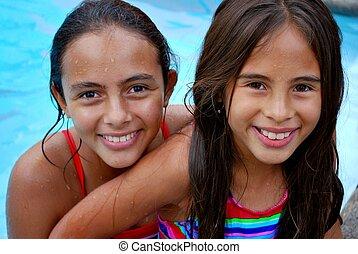 Hispanic girls in the pool - Two Hispanic girls smiling in ...
