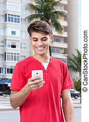 Hispanic guy in the city typing message at phone