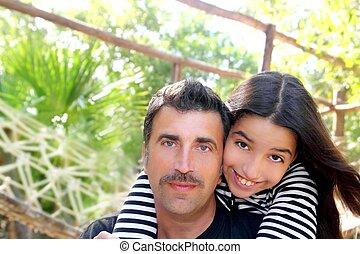 Hispanic latin father and teen daughter hug park